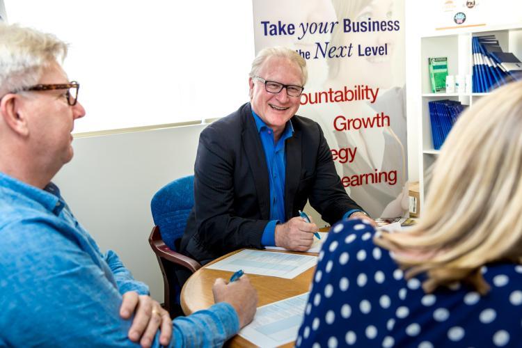 Smiling Facilitator of a Board Meeting in Australia